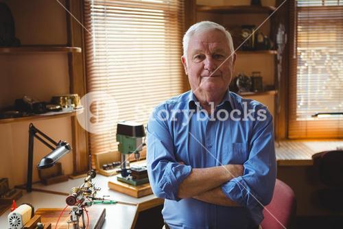 Portrait of horologist standing with arms crossed