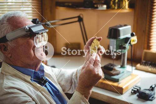 Horologist examining a clock part