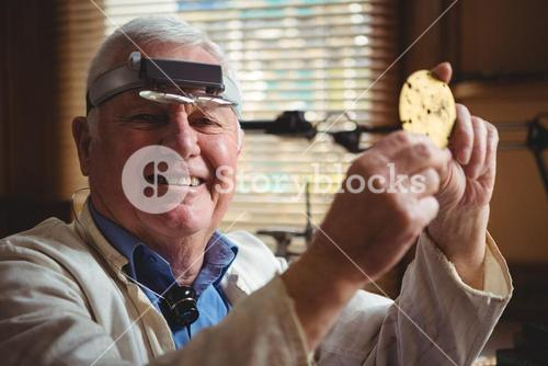 Smiling horologist examining clock parts in workshop