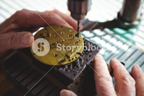 Hands of horologist drilling a dial plate