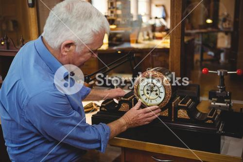 Horologist checking a clock in workshop