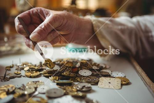 Horologist selecting a clock dial with tweezers