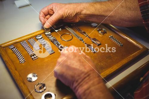 Horologist arranging watch strap on wooden board
