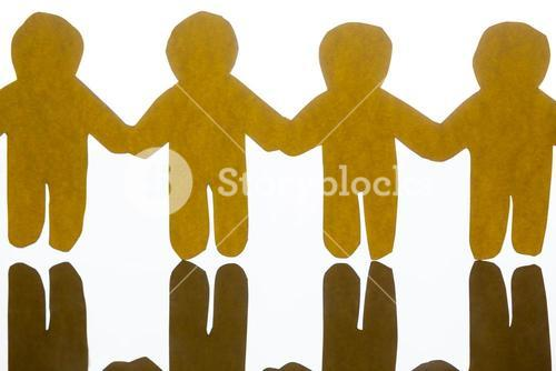 Paper cut outs holding hands together on white background