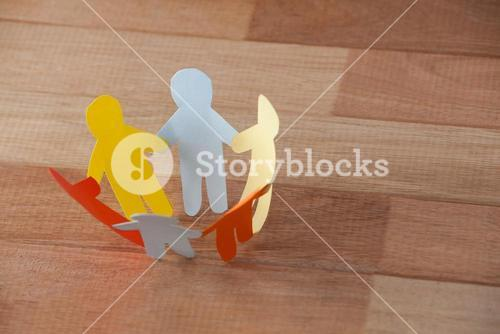 Multicolored paper cut outs forming a circle on wooden background