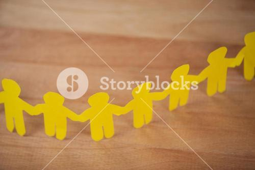 Paper cut outs forming a human chain on wooden table