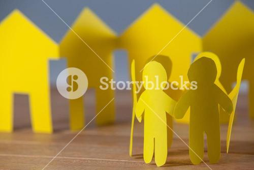 Paper cutout people standing in a circle against paper houses