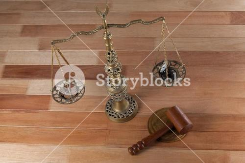 Conceptual image of watch and coins on the justice scale