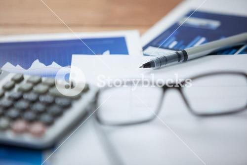 Paper document with business graph, pen, calculator and spectacles