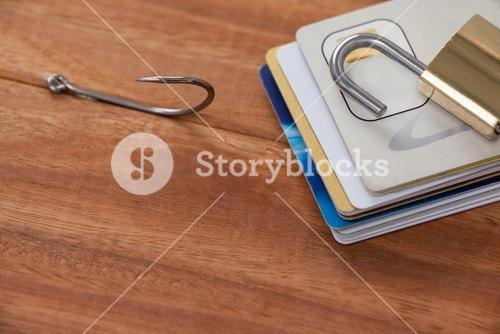 Bunch of credit cards, fishing hook and lock on wooden background