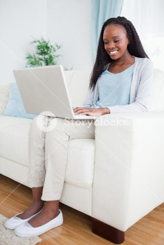 Woman on couch looking at computer screen