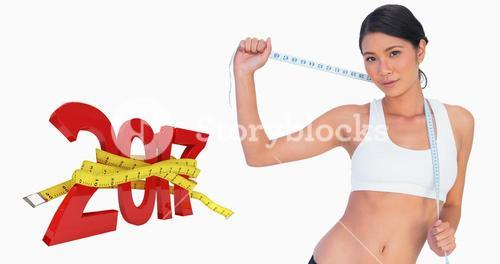 Composite image of self confident slim woman holding her measuring tape
