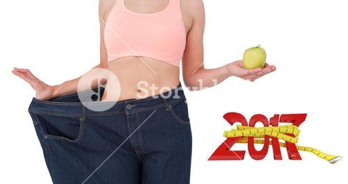 Composite image of woman showing her waist after losing weight