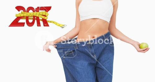 Composite image of mid section of slim woman wearing too big jeans holding an apple