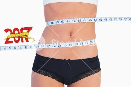 Composite image of slim belly surrounded by measuring tape