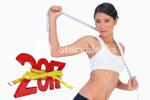 Composite image of slim woman holding her measuring tape
