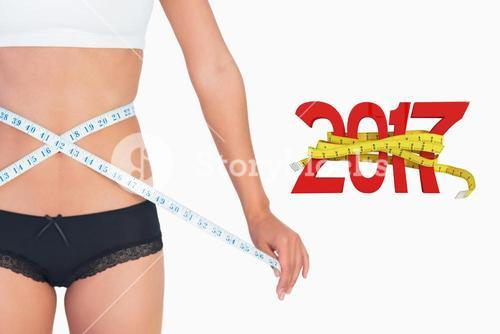 Composite image of cheerful slim woman measuring her waist