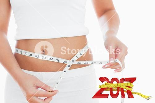Composite image of midsection of woman measuring waist