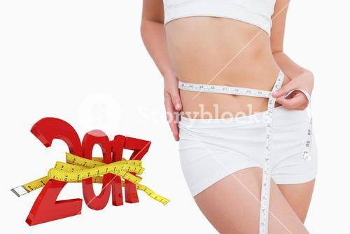 Composite image of fit woman measuring waist with measuring tape