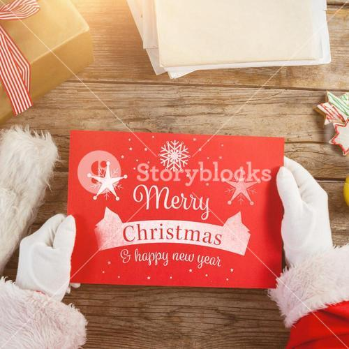 Composite image of santa claus holding a red placard