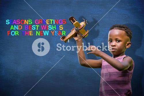 Composite image of child holding wooden airplane