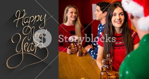 Composite image of friends having beers during christmas