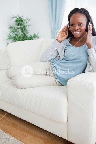 Woman relaxing on couch with music