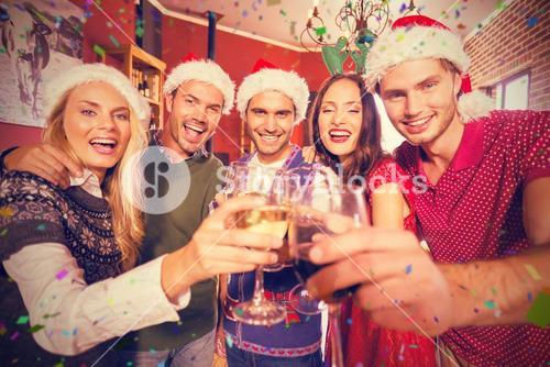 Composite image of portrait of friends wearing christmas hats toasting