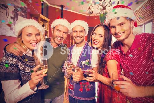 Composite image of portrait of friends wearing christmas hats with champagne flute
