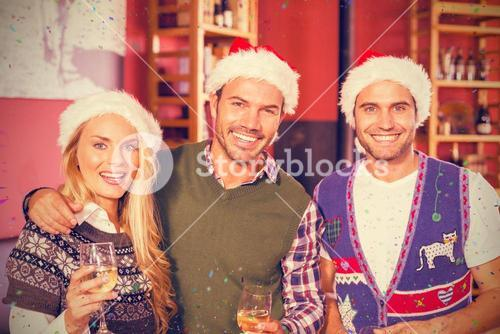 Composite image of portrait of friends wearing christmas hats