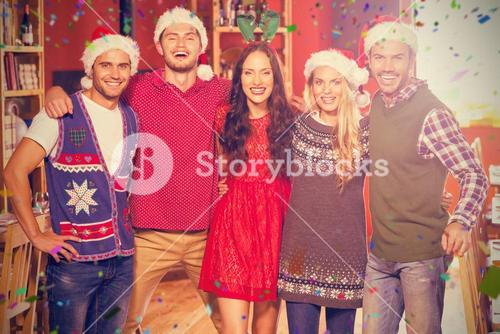 Composite image of portrait of friends wearing christmas hats standing together