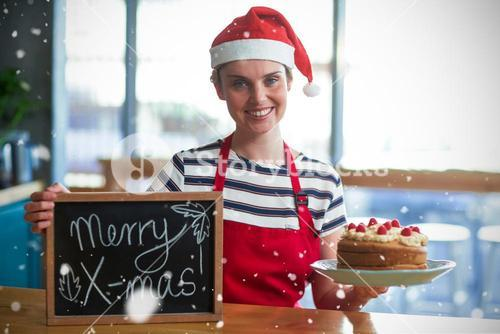 Composite image of portrait of waitress holding slate with merry x-mas sign and cake