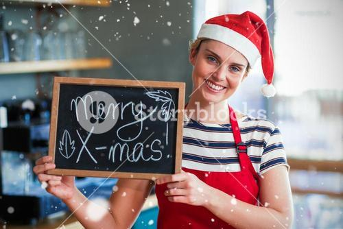Composite image of portrait of waitress showing slate with merry x-mas sign