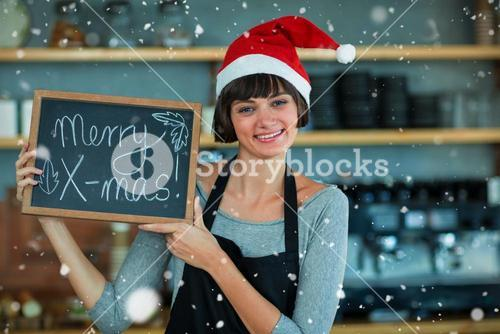 Composite image of portrait of waitress showing slate with merry x-mas text
