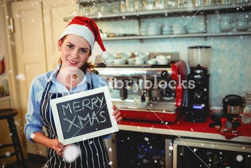 Composite image of portrait of barista holding christmas sign at cafe