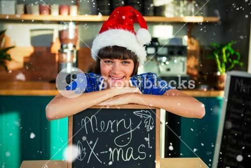 Composite image of portrait of smiling waitress wearing santa hat and sitting with x-mas sign board