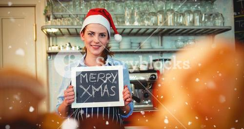 Composite image of portrait of happy barista holding christmas at cafe