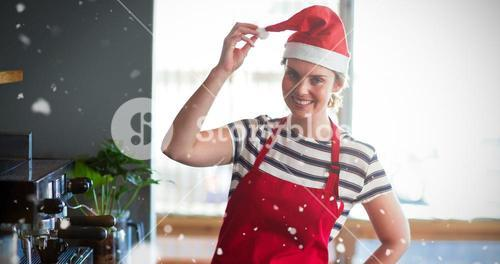 Composite image of portrait of waitress in santa hat standing with hand on hip