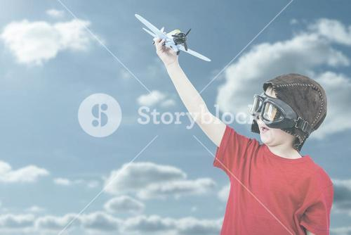 Composite image of boy playing with toy airplane