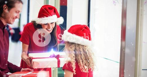 Composite image of parents giving christmas gifts to their daughter