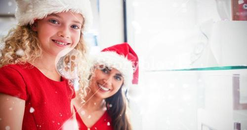 Composite image of portrait of smiling mother and daughter in christmas attire