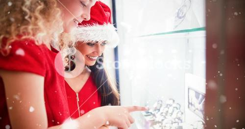 Composite image of side view of mother and daughter in christmas attire looking at wrist watch displ