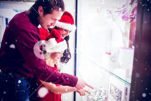 Composite image of side view of family in christmas attire looking at display of wrist watch