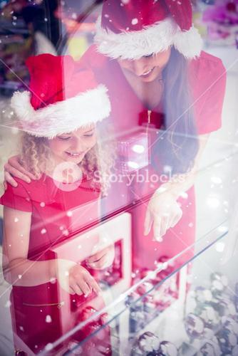 Composite image of mother and daughter in christmas attire looking at wrist watch display