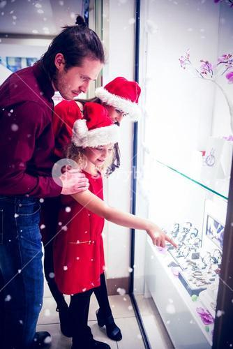 Composite image of family in christmas attire looking at display of wrist watch