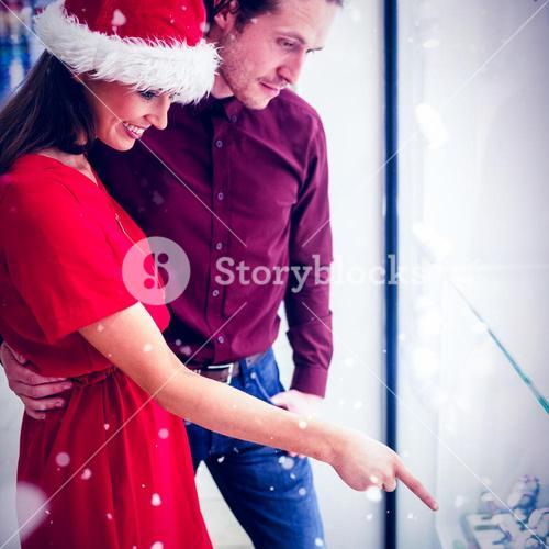 Composite image of side view of couple in christmas attire looking at wrist watch display