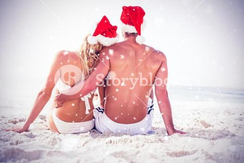 Composite image of rear view of couple with santa hat sitting together at beach