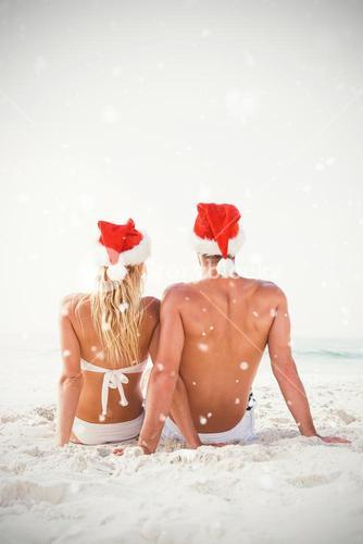 Composite image of couple wearing santa hat at beach