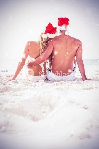 Composite image of rear view of couple wearing santa hat on beach