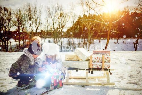 Composite image of brother and sister opening present while crouching at snow field